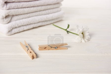close-up view of clothespins, beautiful chamomile flower and clean soft towels on white wooden table