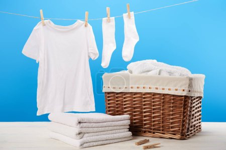 laundry basket, pile of clean soft towels and white clothes hanging on clothesline on blue