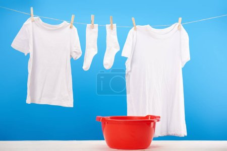 red basin and clean white clothes hanging on clothesline on blue