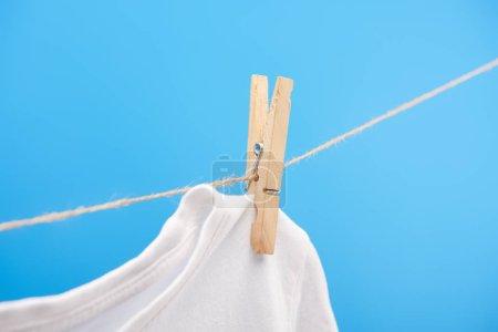 Photo pour Vue rapprochée du t-shirt blanc propre avec une pince à linge suspendue à une corde isolée sur bleu - image libre de droit