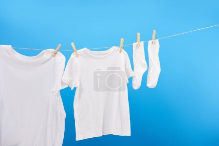 Photo for Clean white t-shirts and socks hanging on clothesline isolated on blue - Royalty Free Image