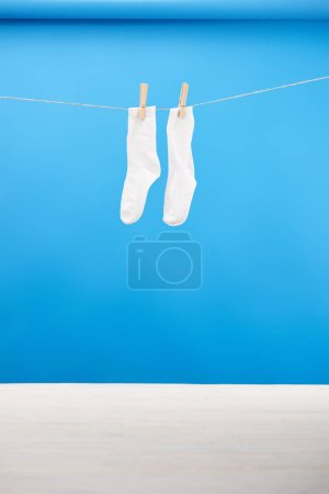 clean white socks hanging on clothesline on blue