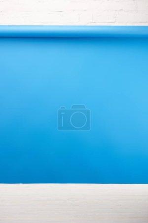 Photo pour Fond bleu et surface en bois clair au mur de briques blanches - image libre de droit