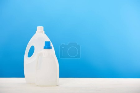 Photo for Close-up view of plastic containers with laundry liquids on blue - Royalty Free Image