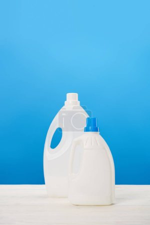 Photo for Plastic containers with laundry liquids on blue - Royalty Free Image