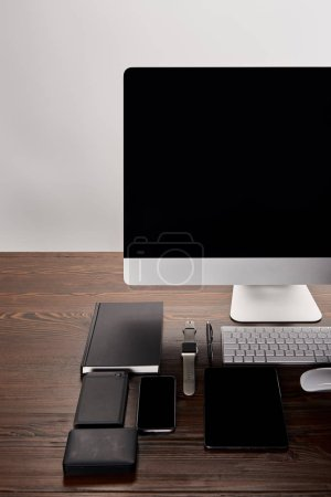 Photo for Monoblock computer with various devices on wooden table isolated on grey - Royalty Free Image