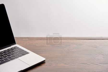Photo for Partial view of laptop on wooden table isolated on grey - Royalty Free Image