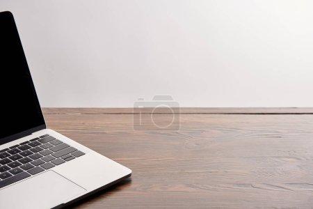 Foto de Vista parcial del portátil en la mesa de madera aislado en gris - Imagen libre de derechos