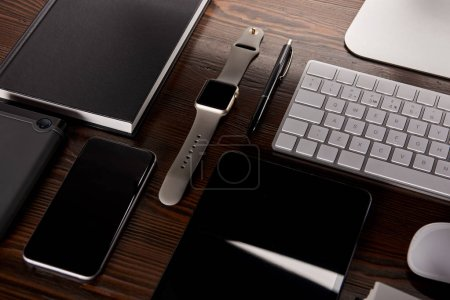 close-up shot of modern workplace with various devices on wooden desk