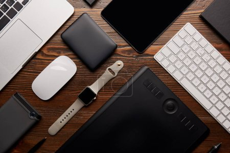Photo for Flat lay with different devices on wooden workplace - Royalty Free Image