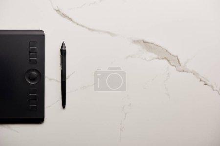 vue de dessus de tablette graphique sur la surface du marbre blanc