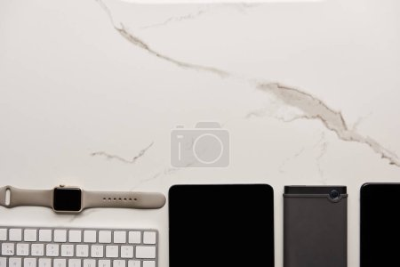 top view of various wireless gadgets on white marble surface