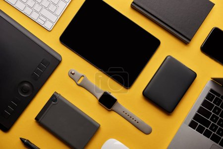 Photo for Flat lay with different wireless devices on yellow surface - Royalty Free Image