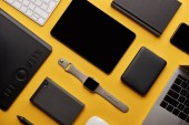 flat lay with different wireless devices on yellow surface