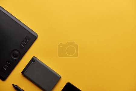 top view of graphics tablet and portable hdd on yellow surface