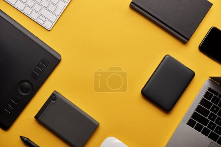 top view of different wireless gadgets on yellow surface