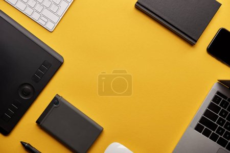 top view of various wireless gadgets on yellow surface