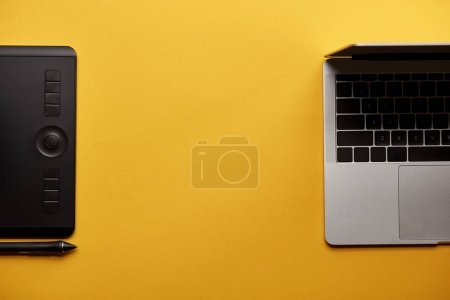top view of opened laptop and graphics tablet on yellow surface