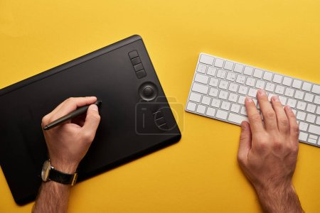 cropped shot of designer drawing with graphics tablet and keyboard on yellow surface