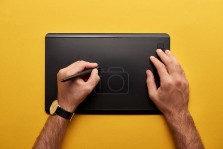 cropped shot of designer drawing with graphics tablet on yellow surface