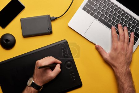 cropped shot of graphics designer working with laptop and graphics tablet on yellow surface