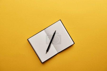 Photo pour Vue du dessus du bloc-notes et du stylo ouverts sur la surface jaune - image libre de droit