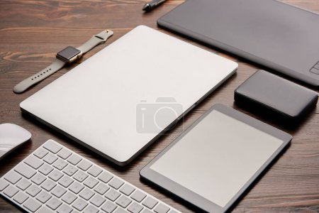 Photo for Close-up shot of various wireless gadgets and graphics tablet on wooden desk - Royalty Free Image