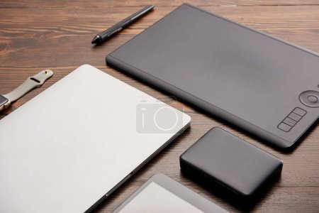 close-up shot of various wireless devices and graphics tablet on wooden desk