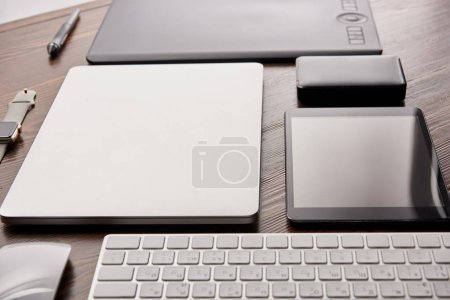 Photo for Close-up shot of different wireless devices and graphics tablet on wooden desk - Royalty Free Image