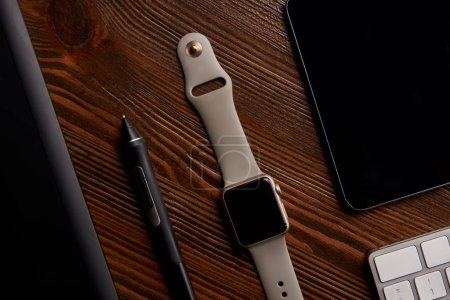 top view of smart watch with wireless keyboard, digital and graphics tablet on wooden table