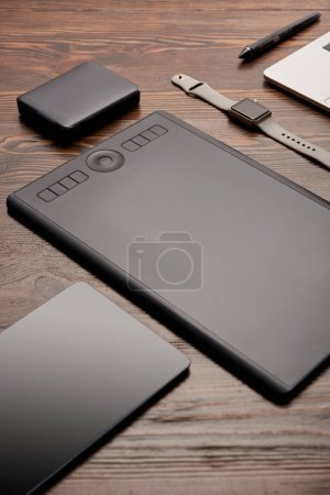 close-up shot of professional graphics tablet with different gadgets on wooden table