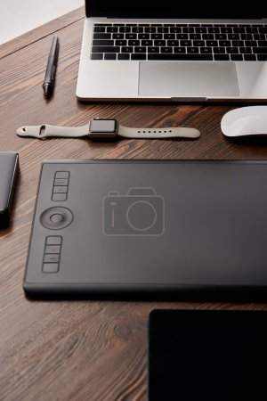 close-up shot of professional graphics tablet with various gadgets on wooden table