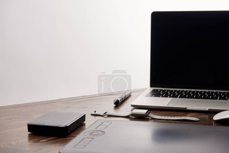 close-up shot of cg artist gadgets on wooden table isolated on grey