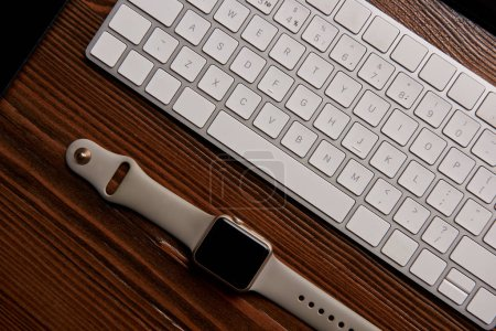 Photo for Top view of wireless keyboard and smart watch on wooden table - Royalty Free Image