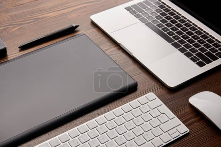 close-up shot of laptop with wireless keyboard and graphics tablet on wooden table