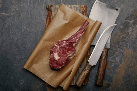 top view of raw rib eye steak on baking paper with kitchen knives on grey background