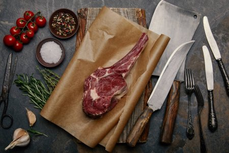 Photo for Top view of raw rib eye steak on baking paper with variety of kitchen knives, spices, herbs and tomatoes on grey background - Royalty Free Image