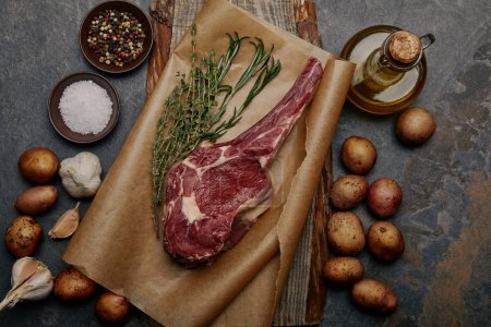 raw rib eye steak on baking paper with spices, herbs and potatoes on grey background