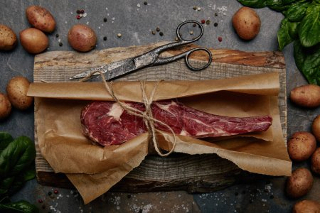 top view of raw rib eye steak wrapped in baking paper on wooden board with spices and potatoes