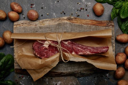 raw rib eye steak wrapped in baking paper on wooden board with spices and potatoes