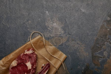 top view of raw meat steak on baking paper on grey background