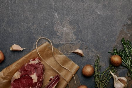 top view of raw meat steak on baking paper with potatoes on grey background