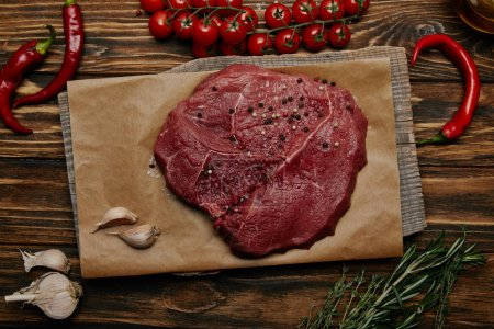 flat lay with fresh raw meat on baking paper with garlic and vegetables on wooden background