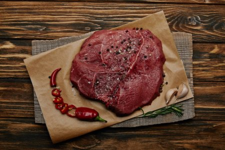 top view of fresh raw meat on baking paper with chopped chilli pepper and garlic on wooden background