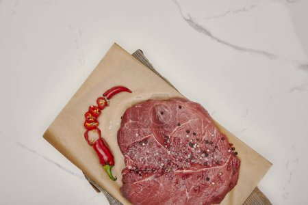 top view of fresh raw meat on baking paper with chopped chilli pepper on white background