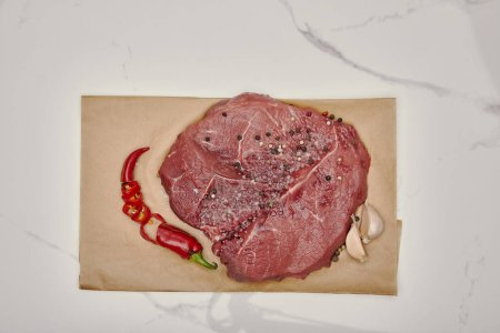 top view of fresh raw meat on baking paper with chopped chilli pepper and garlic on white background