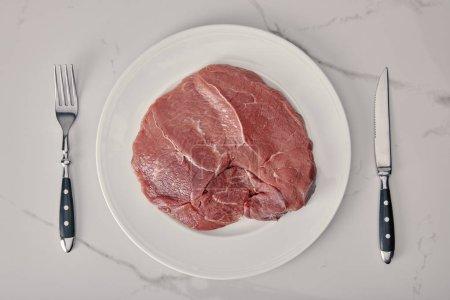 Ansicht von frischem rohem Fleisch auf Teller mit Küchenbesteck auf weißem Hintergrund