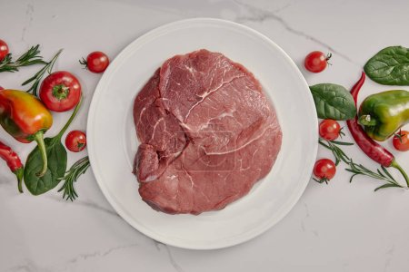 Photo for Top view of fresh raw meat on plate with vegetables and herbs on white background - Royalty Free Image