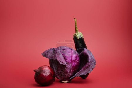 close-up view of fresh ripe organic onion, cabbage and eggplant on red background
