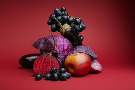 close-up view of fresh ripe grapes, apple, cabbage, beetroot, onion and eggplants on red background